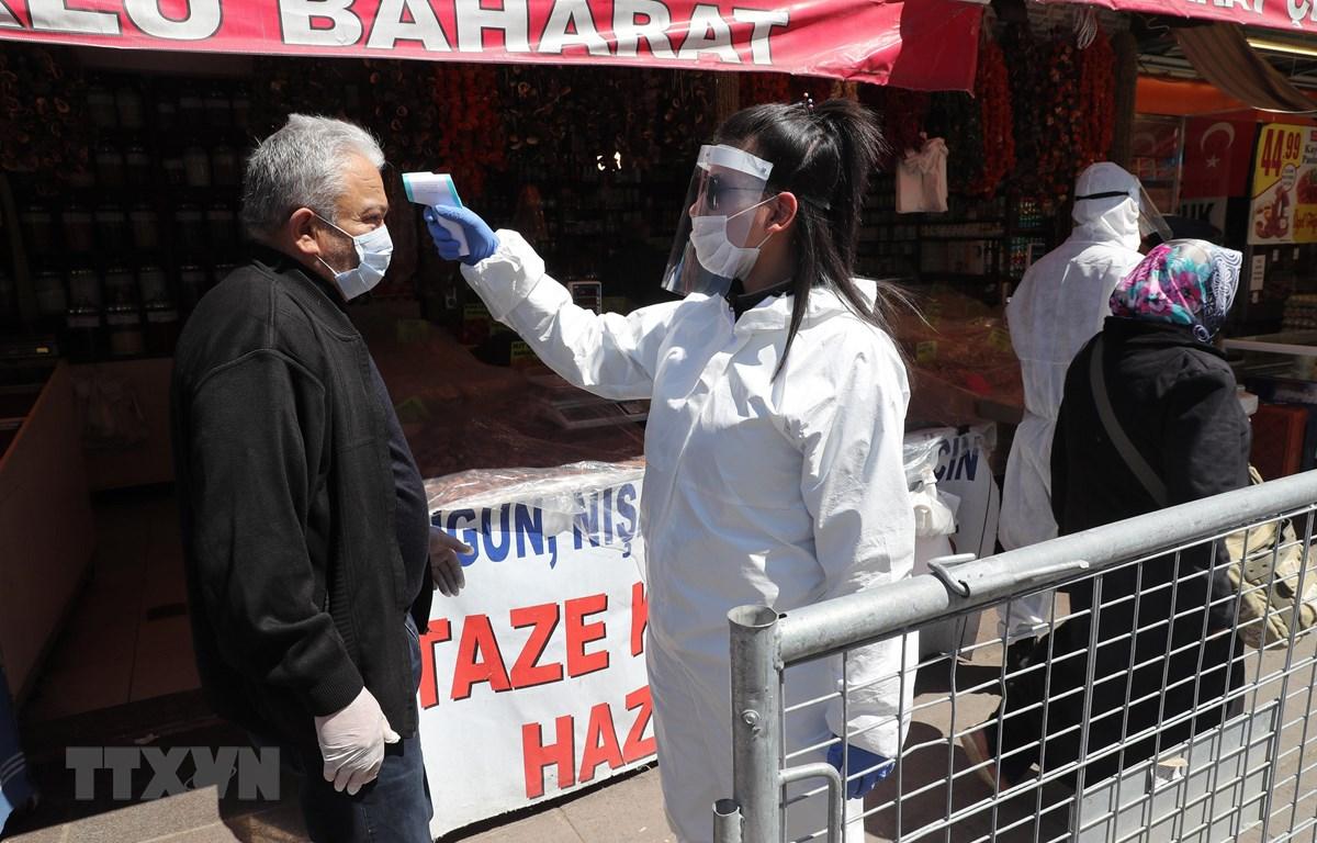 Kiểm tra thân nhiệt nhằm ngăn chặn sự lây lan của dịch COVID-19 tại một chợ ở Ankara, Thổ Nhĩ Kỳ, ngày 17/4/2020. (Ảnh: THX/TTXVN)