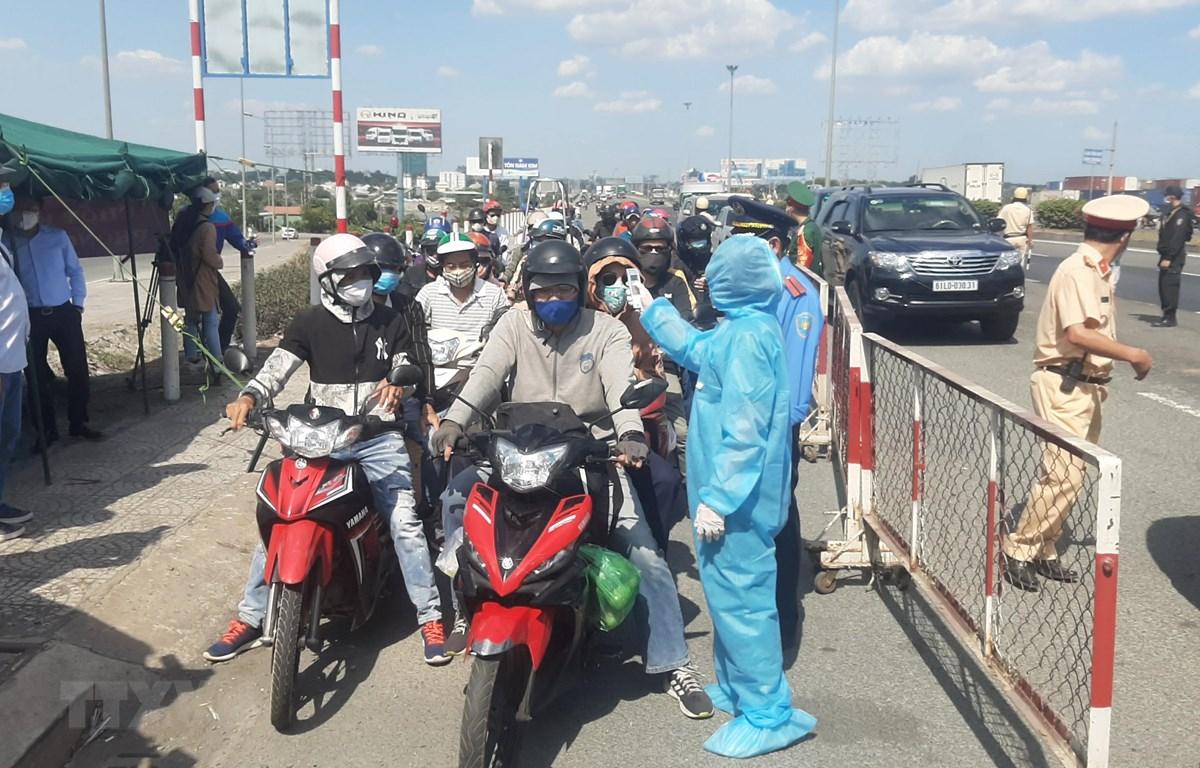 Nhân viên y tế đo thân nhiệt người ra vào thành phố Hồ Chí Minh tại chốt kiểm dịch. (Ảnh: Đinh Hằng/TTXVN)