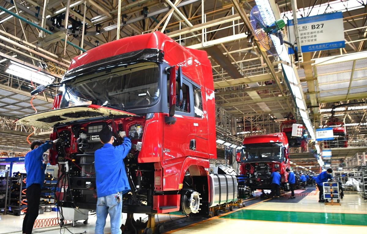 Công nhân làm việc tại dây chuyền sản xuất xe tải hạng nặng của Tập đoàn sản xuất ôtô Thiểm Tây, Trung Quốc ngày 23/4/2020. (Ảnh: THX/TTXVN)