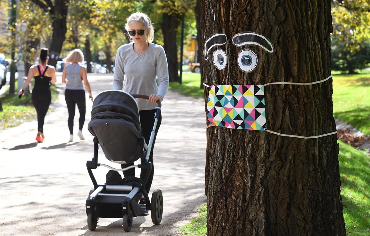 """Người dân Australia dạo chơi tại một công viên sau khi Chính phủ công bố kế hoạch nới lỏng """" an toàn - COVID"""" theo lộ trình 3 giai đoạn tại Melbourne, ngày 8/5/2020. (Ảnh: AFP/TTXVN)"""