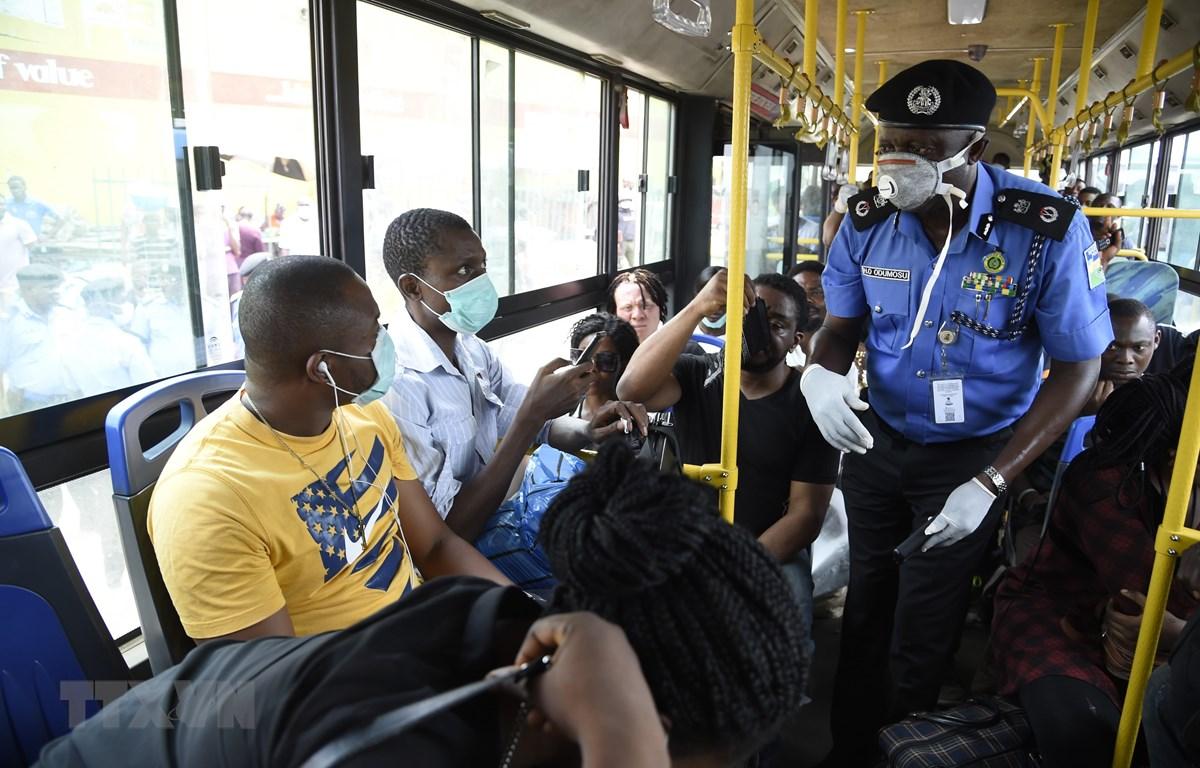 Cảnh sát nhắc nhở người dân các biện pháp phòng lây nhiễm COVID-19 tại Lagos, Nigeria. (Ảnh: AFP/TTXVN)