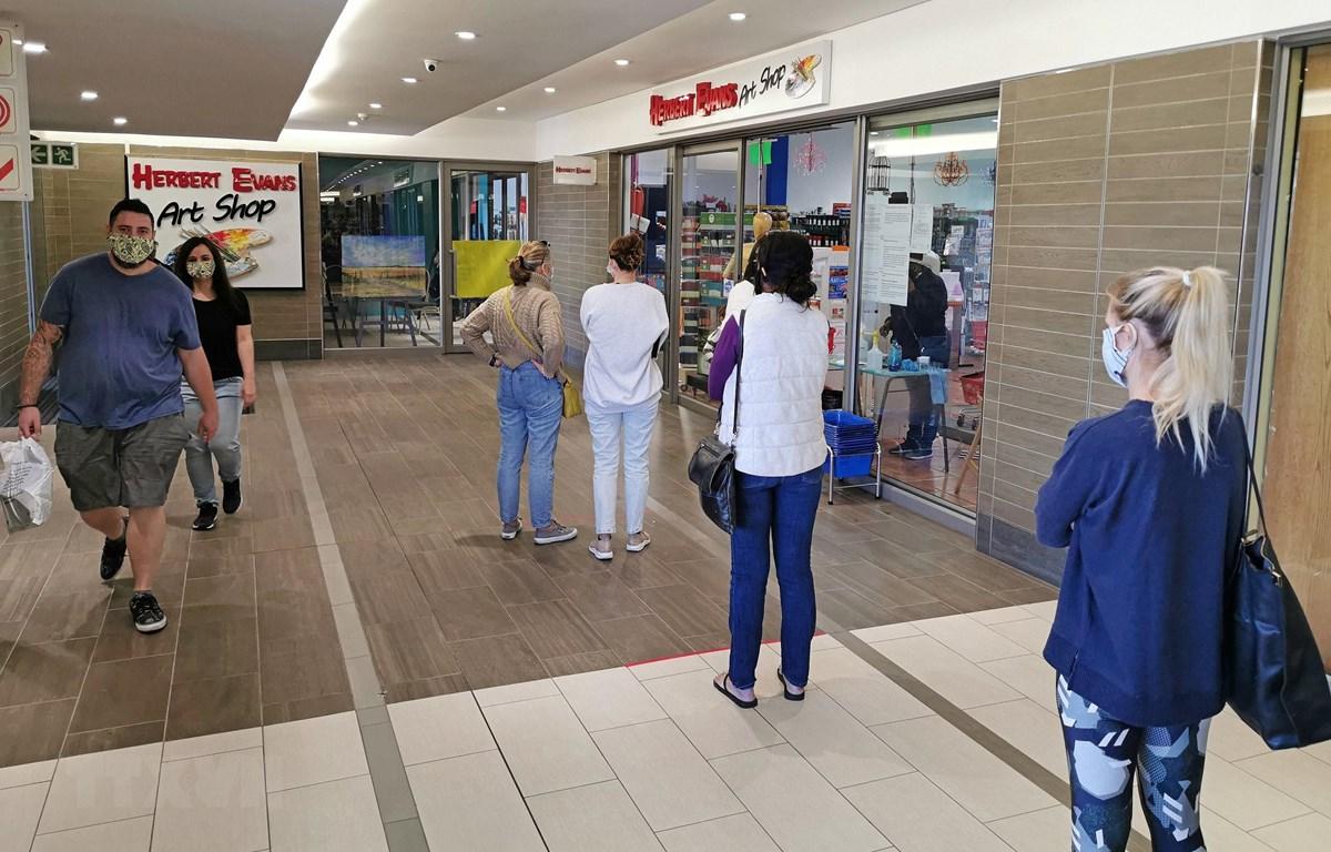 Người dân thực hiện giãn cách xã hội phòng lây nhiễm COVID-19 khi xếp hàng bên ngoài một cửa hàng ở Johannesburg, Nam Phi ngày 2/5/2020. (Ảnh: THX/TTXVN)