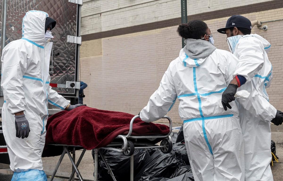 Nhân viên y tế chuyển thi thể bệnh nhân mắc COVID-19 tới nhà tang lễ ở Brooklyn, New York, Mỹ ngày 30/4/2020. (Ảnh: AFP/TTXVN)
