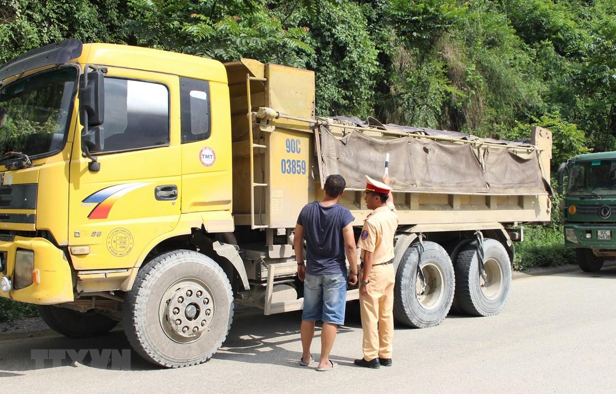 Cảnh sát giao thông kiểm tra một xe tải lưu thông trên đường. Ảnh minh họa. (Nguồn: TTXVN)