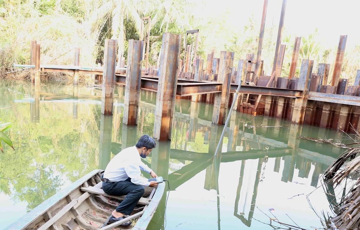 Cán bộ kỹ thuật của Sở Nông nghiệp và Phát triển nông thôn kiểm tra đo độ mặn tại đập ngăn mặn tạm thời trên sông Hàm Luông, xã Đông Sơn, thành phố Bến Tre. (Ảnh: Vũ Sinh/TTXVN)