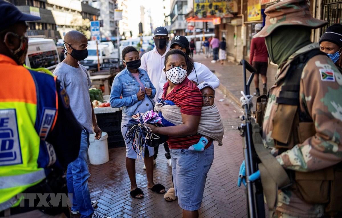 Binh sỹ Nam Phi tuần tra tại một khu chợ ở thủ đô Johannesburg để khuyến cáo người dân tránh tụ tập đông người nhằm ngăn dịch COVID-19 lây lan. (Ảnh: AFP/TTXVN)