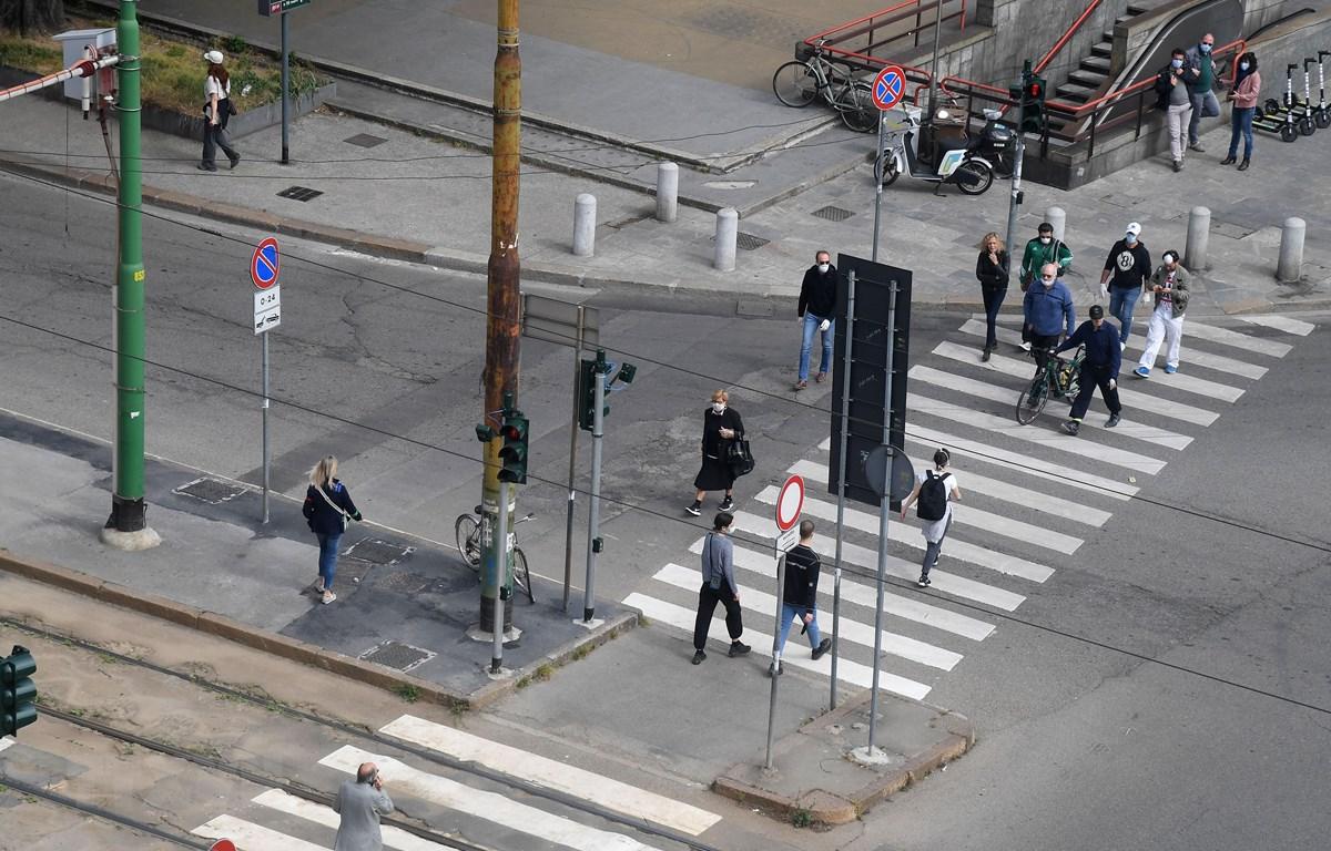 Người dân di chuyển trên đường phố tại Milan, Italy, ngày 4/5/2020. (Ảnh: THX/TTXVN)