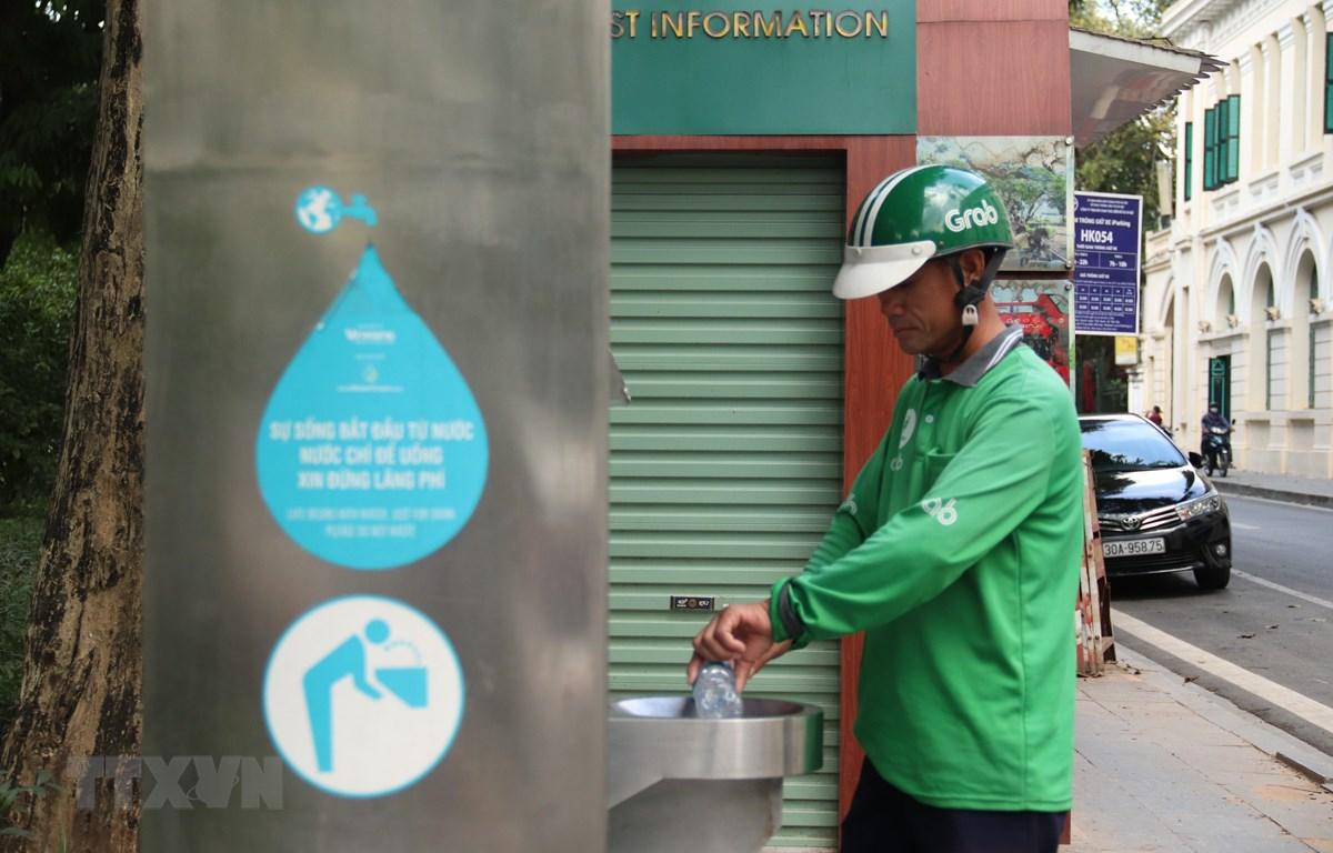 Người dân sử dụng nước ở trụ nước sạch miễn phí được đặt tại quận Hoàn Kiếm (Hà Nội). (Ảnh: Mạnh Khánh/TTXVN)