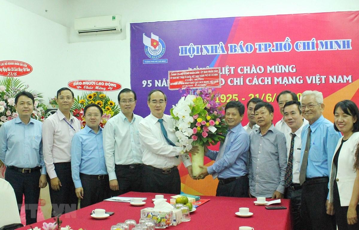 Bí thư Thành ủy Thành phố Hồ Chí Minh Nguyễn Thiện Nhân tặng hoa, chúc mừng Hội Nhà báo Thành phố Hồ Chí Minh. (Ảnh: Thu Hương/TTXVN)