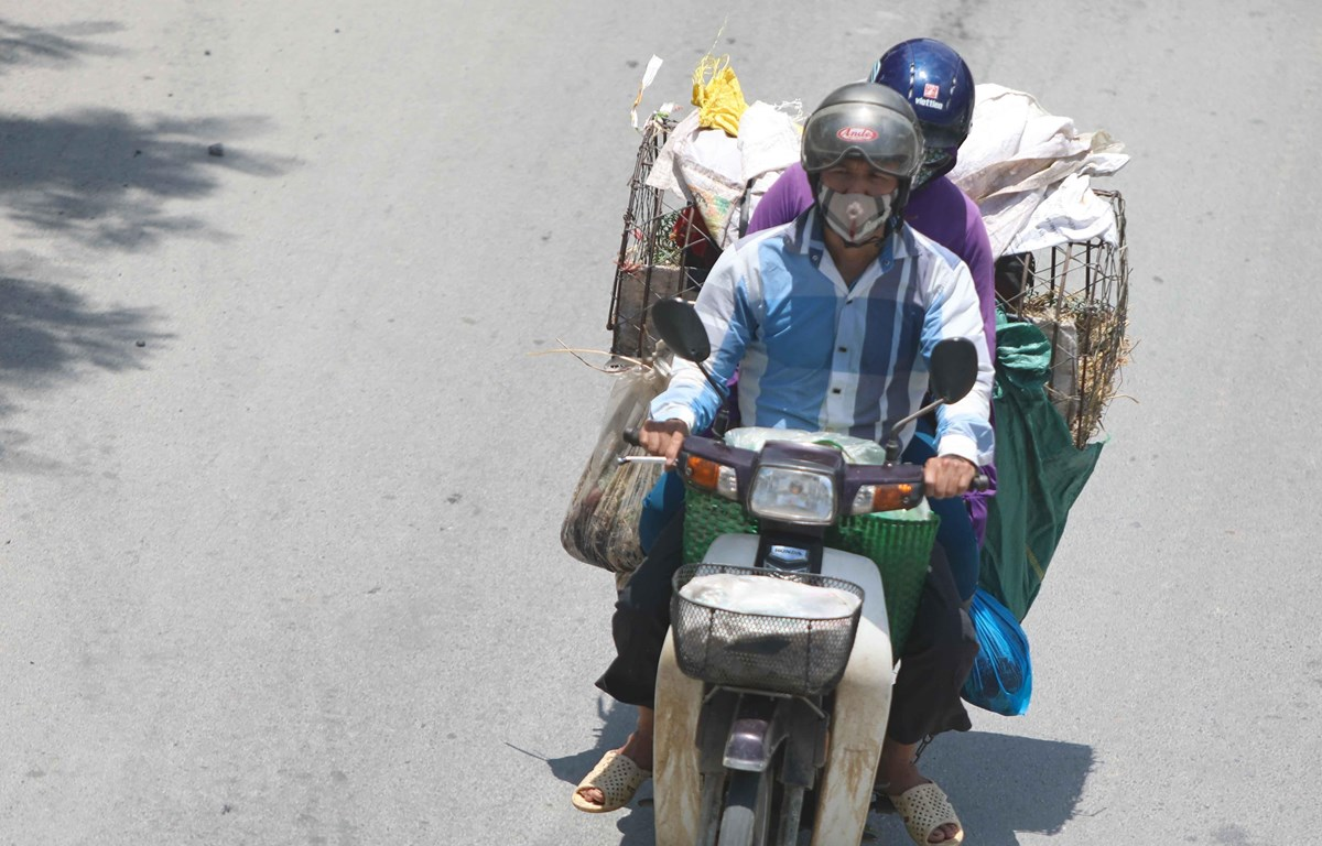 Thời điểm giữa trưa, nếu phải di chuyển trên đường, người dân cần trang bị đồ chống nắng để đảm bảo sức khỏe. (Ảnh: Thanh Tùng/TTXVN)