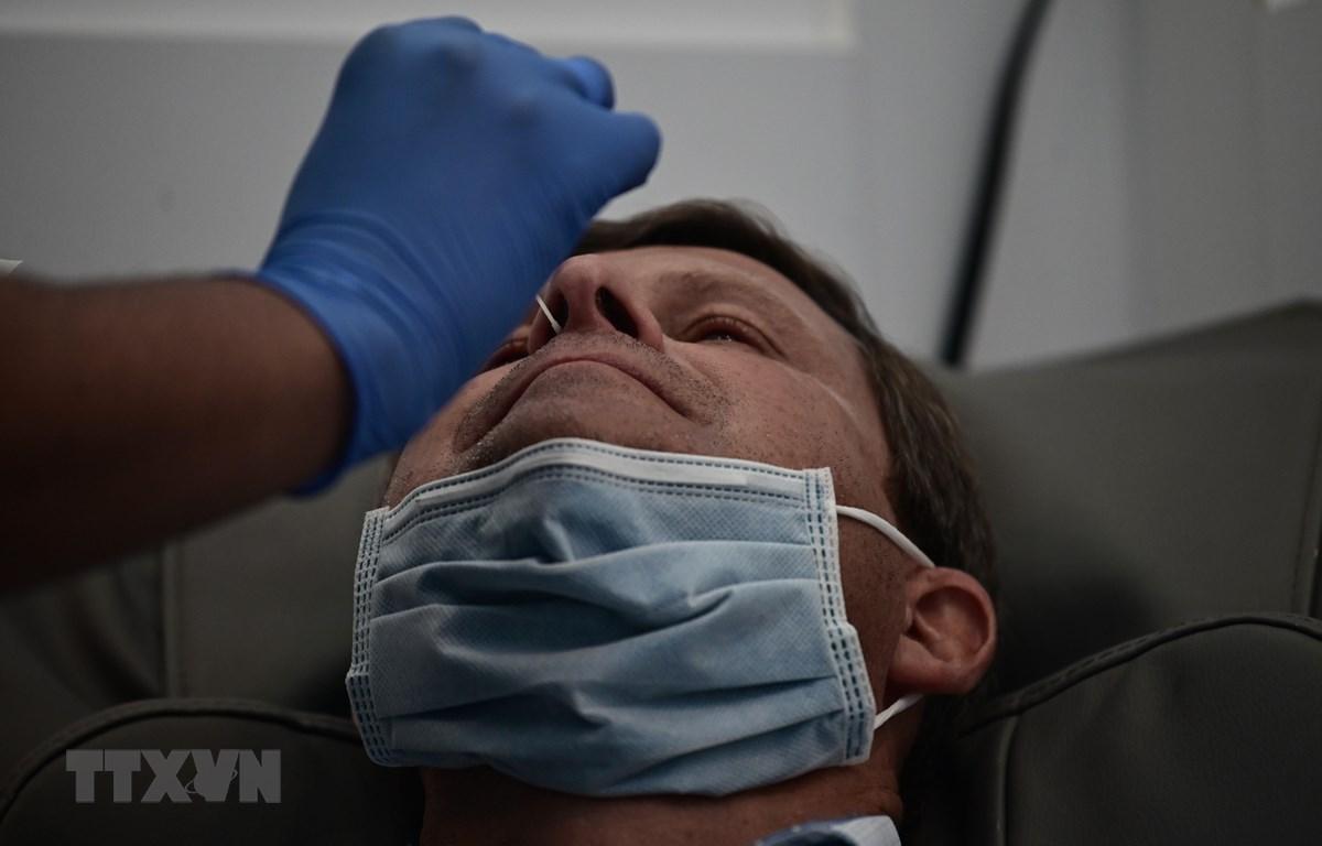 Nhân viên y tế lấy mẫu xét nghiệm COVID-19 cho người dân tại New York, Mỹ. (Ảnh: AFP/TTXVN)