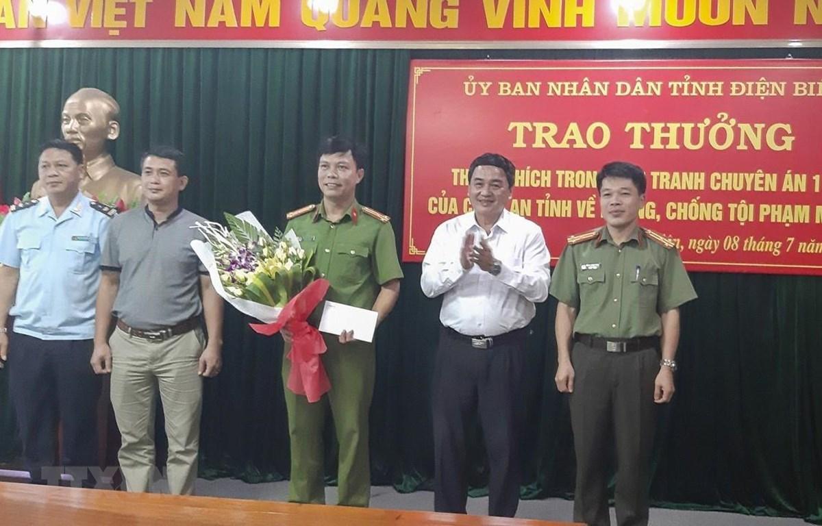 Phó Chủ tịch UBND tỉnh Điện Biên Lê Văn Qúy (thứ 2, từ phải qua trái) khen thưởng cho các thành viên của Ban chuyên án. (Ảnh: TTXVN)