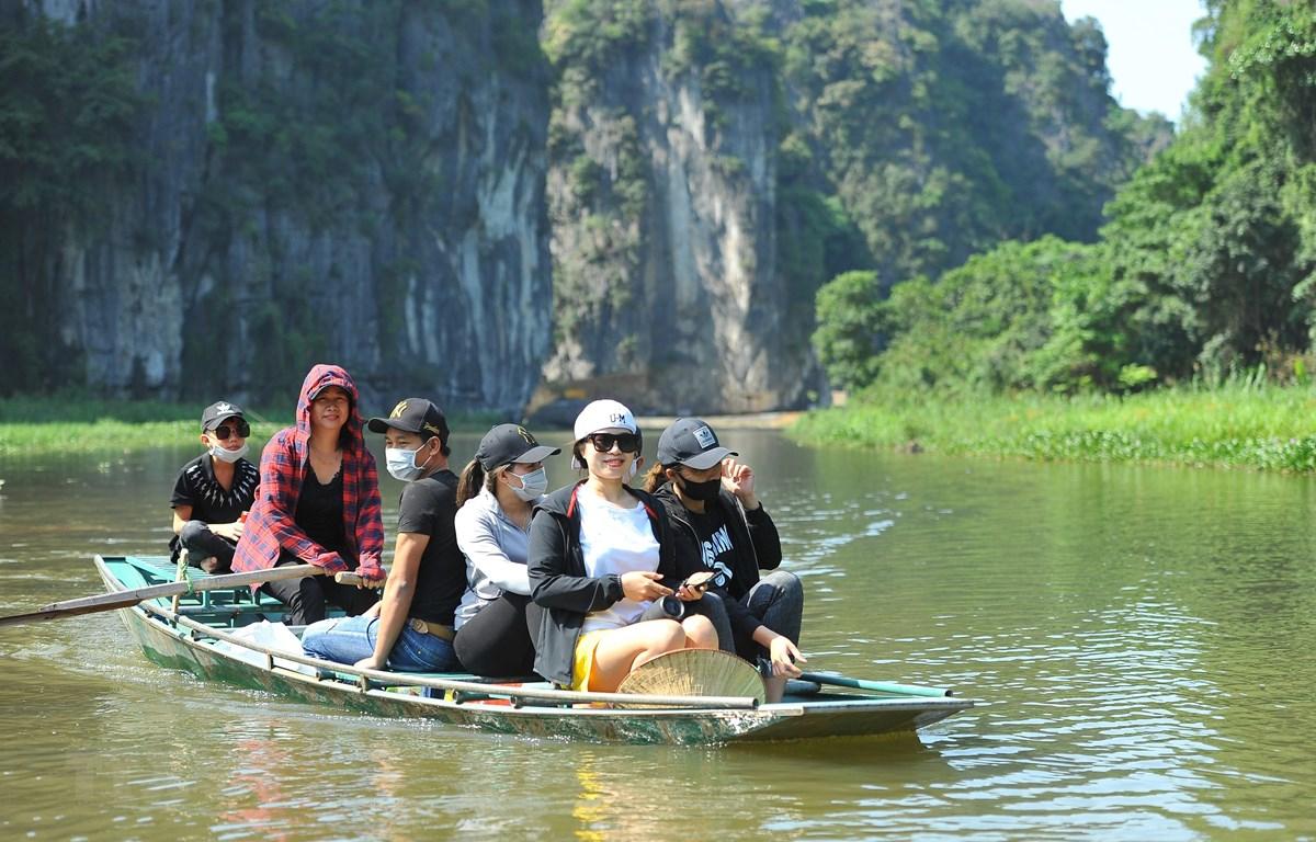 Du khách tham quan khu du lịch Tam Cốc trong ngày đầu được đón khách trở lại. (Ảnh: Minh Đức/TTXVN)