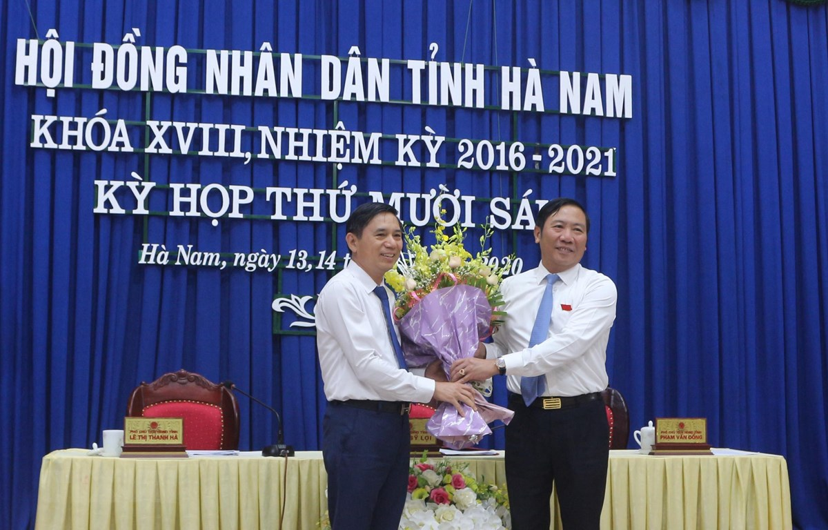 Ông Phạm Sỹ Lợi, Phó Bí thư thường trực Tỉnh ủy, Chủ tịch HĐND tỉnh Hà Nam tặng hoa chúc mừng ông Trần Xuân Dưỡng. (Ảnh: Thanh Tuấn/TTXVN)