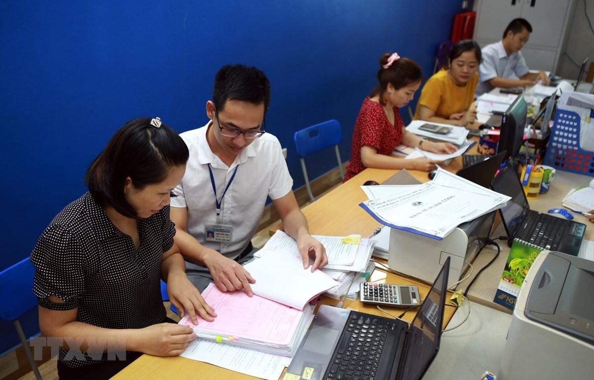 Cán bộ thuế tỉnh Thái Nguyên hướng dẫn doanh nghiệp Công ty CP TM Thép Việt Cường khai báo thủ tục giãn thuế. (Ảnh: Danh Lam/TTXVN)