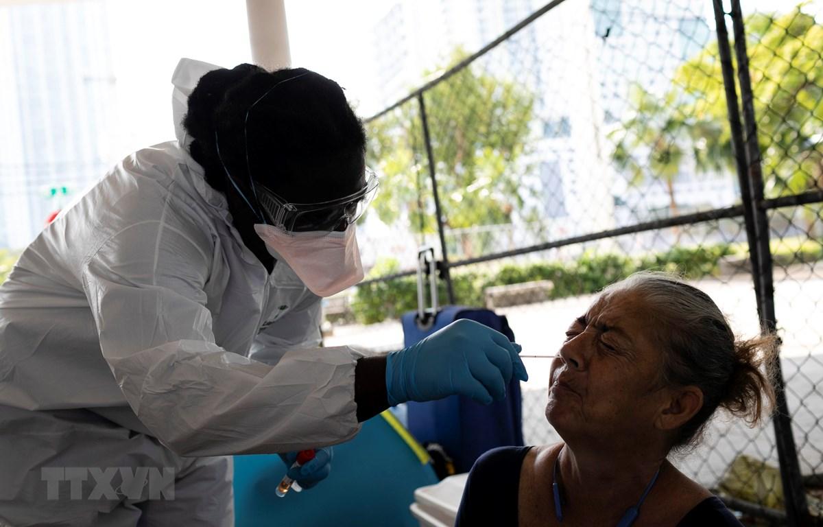 Nhân viên y tế lấy mẫu dịch xét nghiệm COVID-19 cho người dân tại Miami, bang Florida, Mỹ ngày 16/4/2020. (Ảnh: AFP/TTXVN)