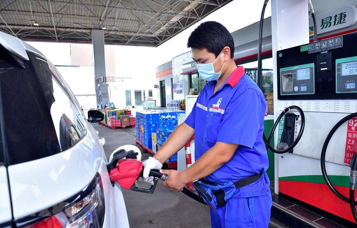 Nhân viên bơm xăng cho phương tiện tại một trạm xăng ở Hà Bắc, Trung Quốc. (Ảnh: THX/TTXVN)