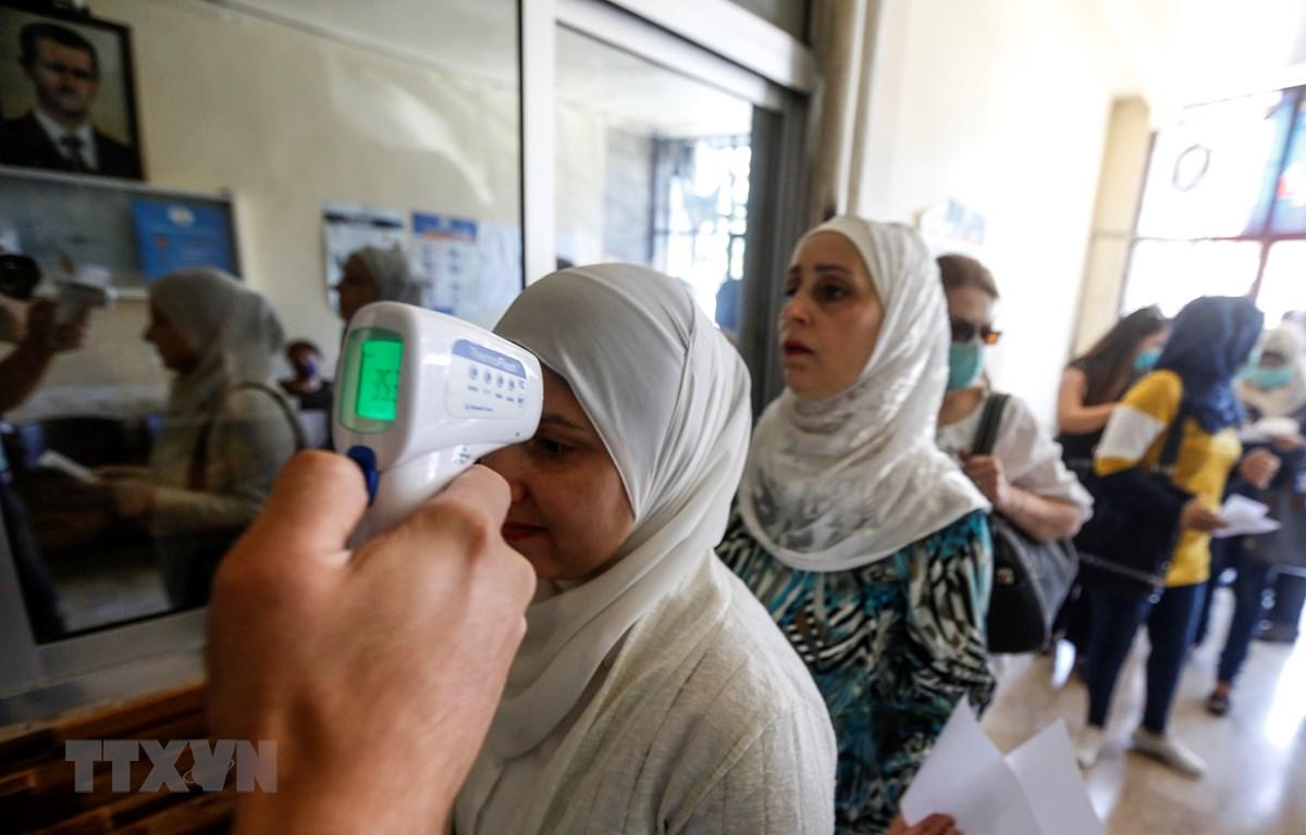 Kiểm tra thân nhiệt phòng lây nhiễm COVID-19 tại một điểm bầu cử ở Damascus, ngày 19/7/2020. (Ảnh: AFP/TTXVN)