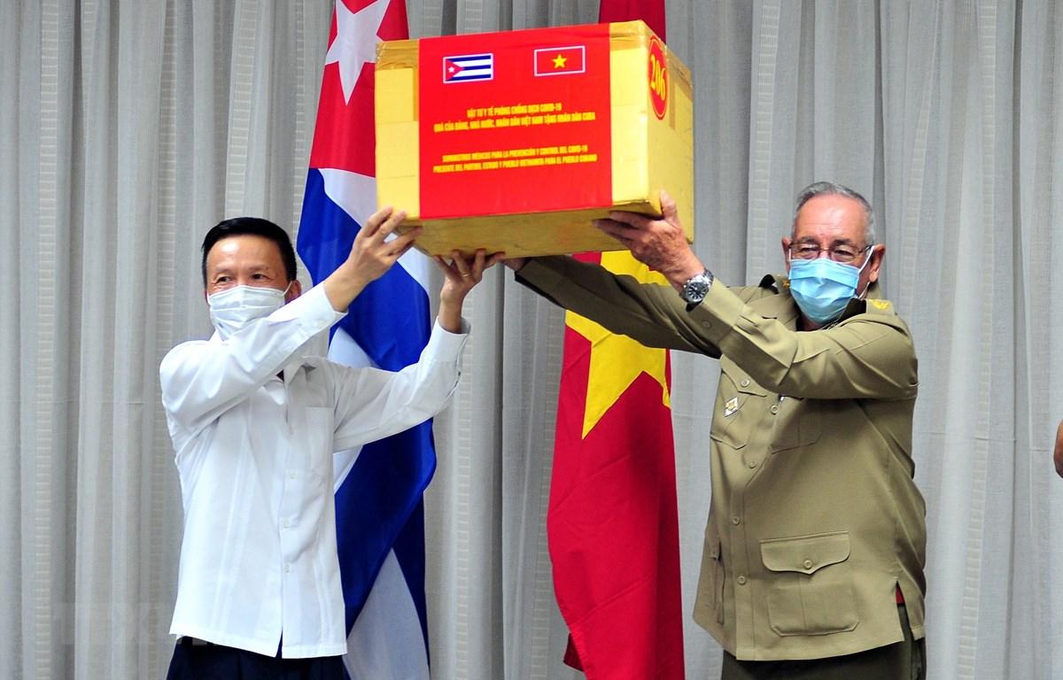 Thượng tướng Ramón Espinosa Martín, Ủy viên Bộ Chính trị, Thứ trưởng Bộ Các lực lượng vũ trang Cuba và Đại biện Đại sứ quán Việt Nam tại Cuba Đỗ Đình Trường trao nhận tượng trưng viện trợ y tế của Việt Nam cho Cuba. (Ảnh: Lê Hà/TTXVN)