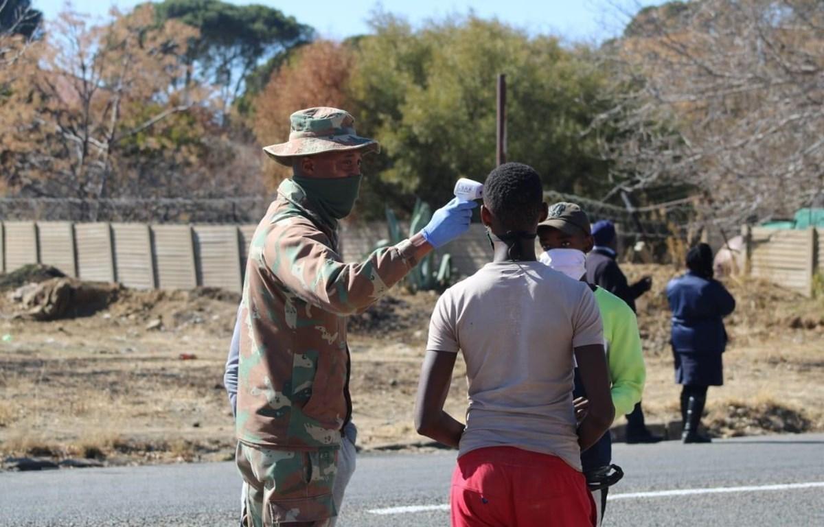 Bính lính Nam Phi thực hiện đo thân nhiệt cho người dân tại ngoại ô thủ đô Pretoria. (Ảnh: Phi Hùng/TTXVN)
