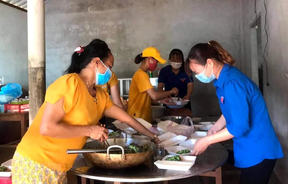 Đoàn Thanh niên và Hội Phụ nữ xã Vĩnh Hòa chuẩn bị những suất ăn, hỗ trợ lực lượng làm nhiệm vụ phong tỏa thôn Đơn Duệ. (Ảnh: TTXVN)