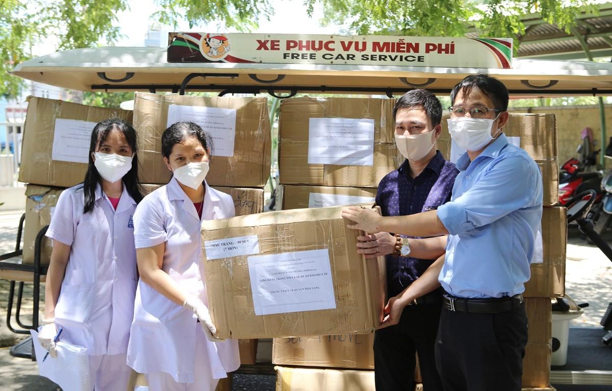 Đại diện Trung tâm Truyền hình Thông tấn và Cơ quan Thông tấn xã Việt Nam Khu vực miền Trung-Tây Nguyên tại Đà Nẵng trao tặng các thùng khẩu trang N95 và đồ bảo hộ y tế cho Trung tâm y tế huyện Hòa Vang. (Ảnh: TTXVN)
