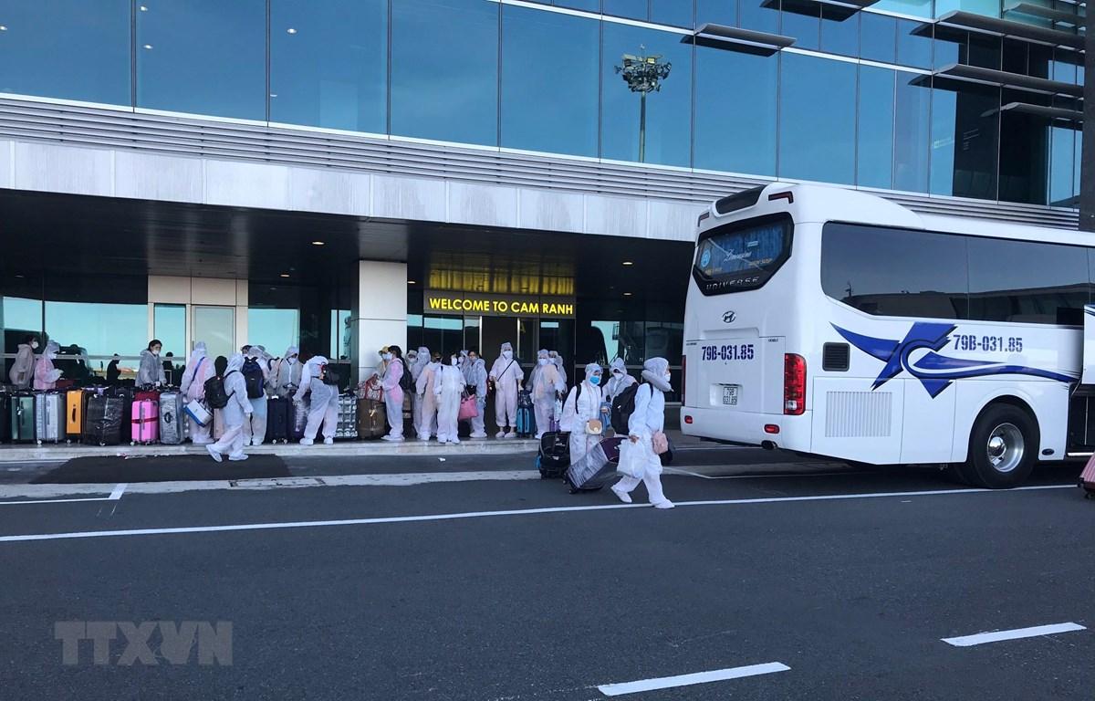 Công dân Việt Nam từ Đài Loan trở về nước lên xe đến các khu cách ly tập trung. (Ảnh: Phan Sáu/TTXVN)
