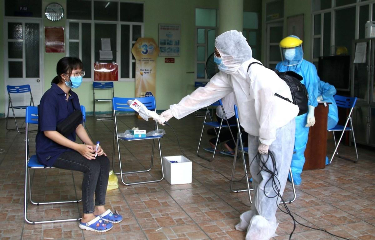 Phóng viên Kênh truyền hình Thông tấn Vnews tác nghiệp an toàn tại khu vực có nguy cơ lây nhiễm. (Ảnh: Quốc Dũng/TTXVN)
