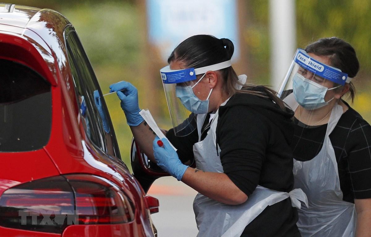 Nhân viên y tế lấy mẫu xét nghiệm COVID-19 cho người dân tại Chessington, phía Tây Nam London, Anh. (Ảnh: AFP/TTXVN)