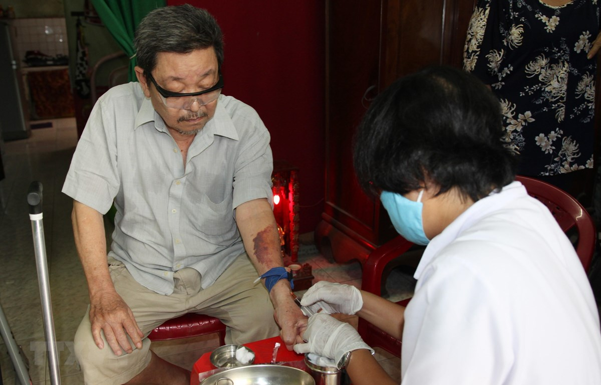 Điều dưỡng Trạm Y tế phường 16, quận Gò Vấp đến nhà lấy máu xét nghiệm cho người bệnh. (Ảnh: Đinh Hằng/TTXVN)