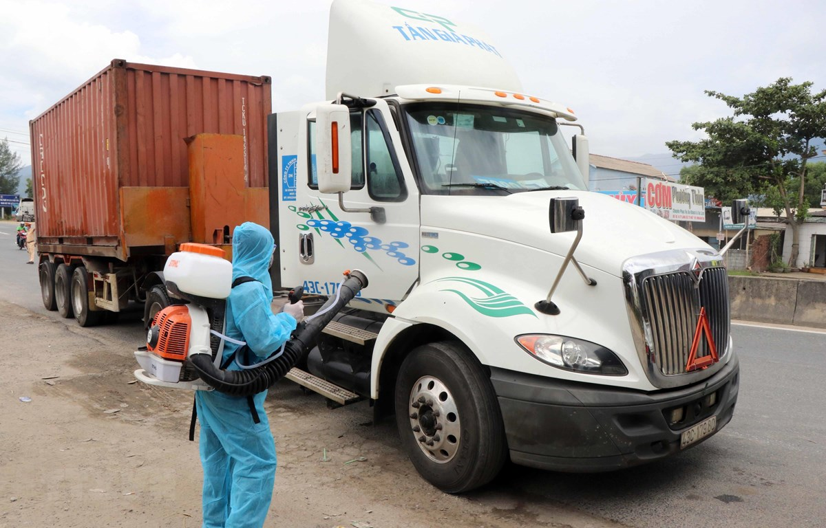 Nhân viên y tế phun thuốc khử khuẩn đối với những xe chở hàng hóa đến từ vùng dịch bệnh tại chốt kiểm soát dịch bệnh số 6 của Thừa Thiên-Huế. (Ảnh: Đỗ Trưởng/TTXVN)