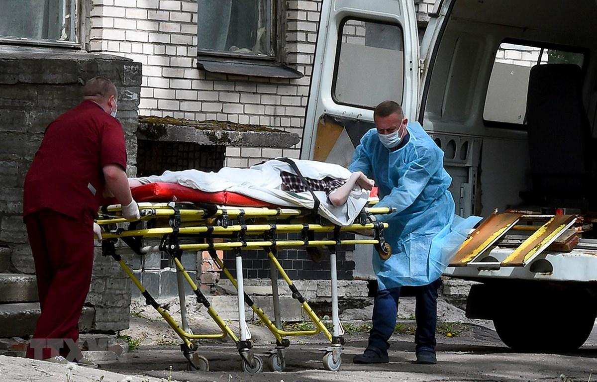 Chuyển bệnh nhân mắc COVID-19 từ xe cứu thương vào một bệnh viện ở Moskva, Nga. (Ảnh: AFP/TTXVN)