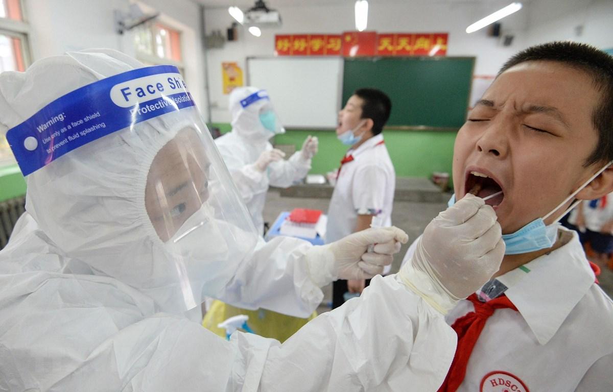 Nhân viên y tế lấy mẫu xét nghiệm COVID-19 tại Handan, tỉnh Hồ Bắc, Trung Quốc. (Ảnh: AFP/TTXVN)