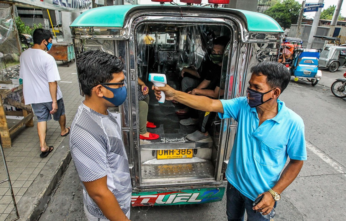 Kiểm tra thân nhiệt nhằm ngăn chặn sự lây lan của dịch COVID-19 tại Manila, Philippines. (Ảnh: THX/TTXVN)