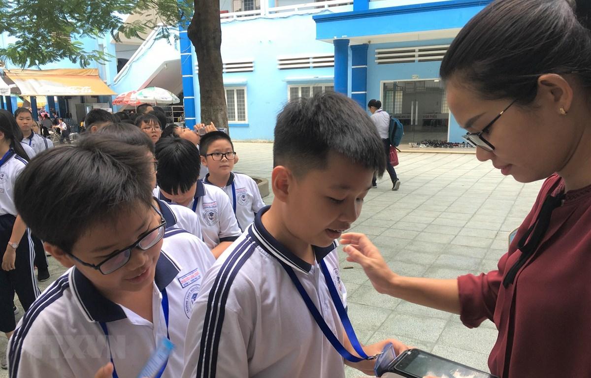 Học sinh Trường Trung học cơ sở Nguyễn Gia Thiều (quận Tân Bình) sử dụng thẻ để nhận suất ăn bán trú. (Ảnh: TTXVN phát)