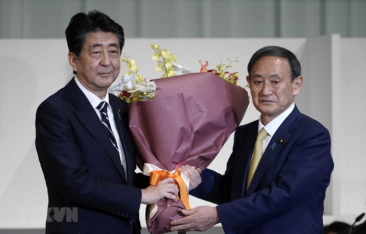 Cựu Thủ tướng Nhật Bản Abe Shinzo (trái) và tân Thủ tướng Nhật Bản Suga Yoshihide. (Ảnh: TTXVN phát)