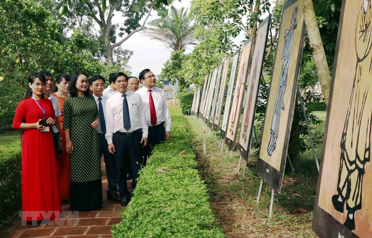 Lãnh đạo tỉnh Hà Tĩnh và du khách xem tranh tại Triển lãm. (Ảnh: Công Tường/TTXVN)