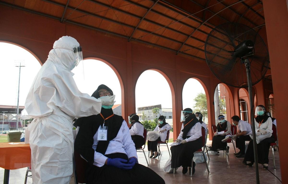 Nhân viên y tế lấy mẫu dịch xét nghiệm COVID-19 cho người dân tại Surabaya, Indonesia, ngày 22/9/2020. (Ảnh: THX/TTXVN)