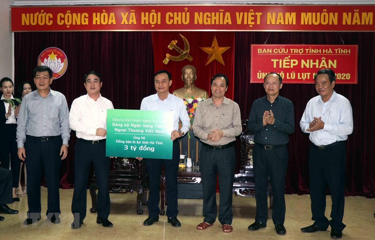 Doanh nghiệp khối cơ quan Trung ương Ngân hàng TMCP Ngoại thương Việt Nam trao tiền ủng hộ cho Hà Tĩnh. (Ảnh: Công Tường/TTXVN)