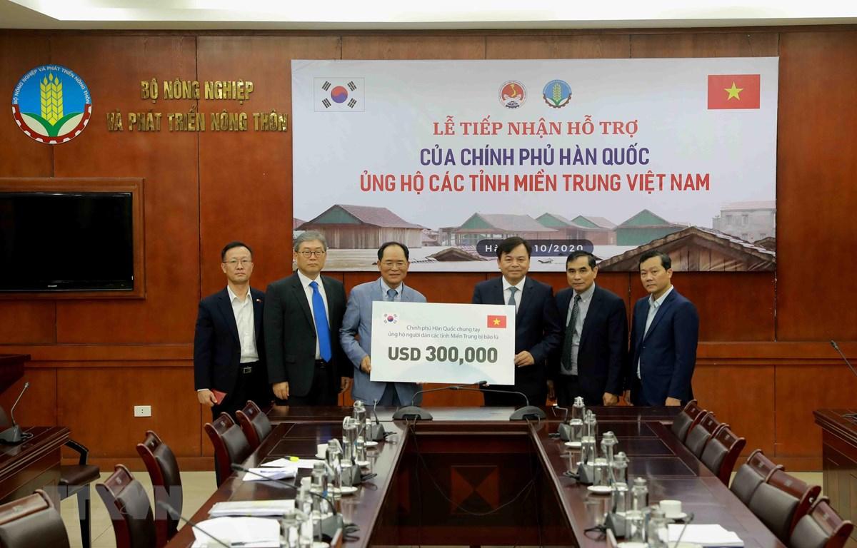 Ông Park Noh-Wan, Đại sứ Hàn Quốc tại Việt Nam trao tượng trưng gói hỗ trợ 300.000 USD cho Ủy viên Ban Chỉ đạo Trung ương về Phòng, chống thiên tai Nguyễn Hoàng Hiệp. (Ảnh: Vũ Sinh/TTXVN)