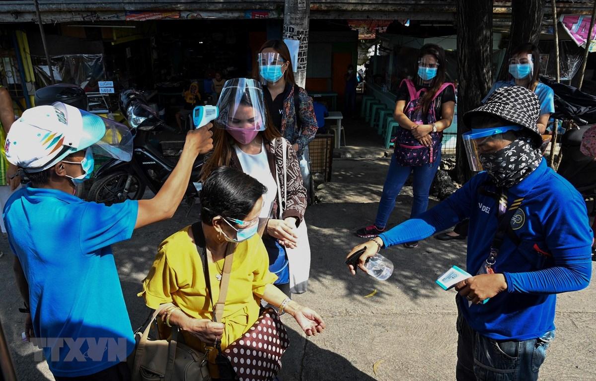 Đo thân nhiệt nhằm ngăn chặn sự lây lan của dịch COVID-19 trước khi lên xe buýt ở Manila, Philippines. (Ảnh: AFP/TTXVN)