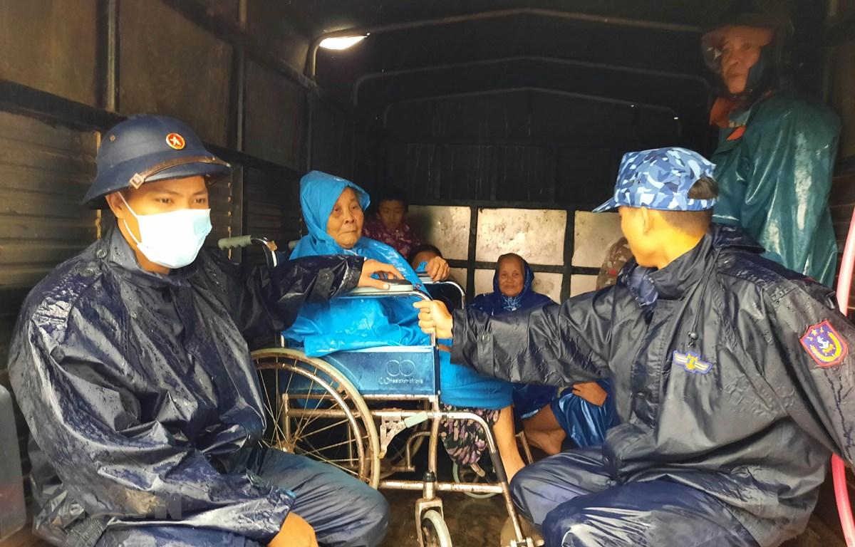 Lực lượng quân đội phối hợp với chính quyền địa phương xã Triệu An, huyện Triệu Phong (Quảng Trị) di chuyển người dân để tránh bão số 13. (Ảnh: Hồ Cầu/TTXVN)