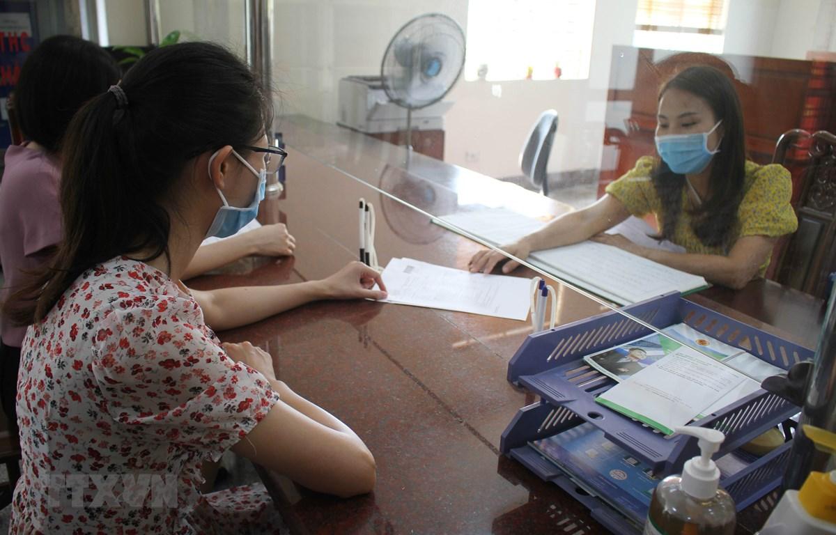 Nhân viên cục thuế tỉnh Ninh Bình hướng dẫn người dân làm thủ tục nộp thuế. (Ảnh: Hải Yến/TTXVN)