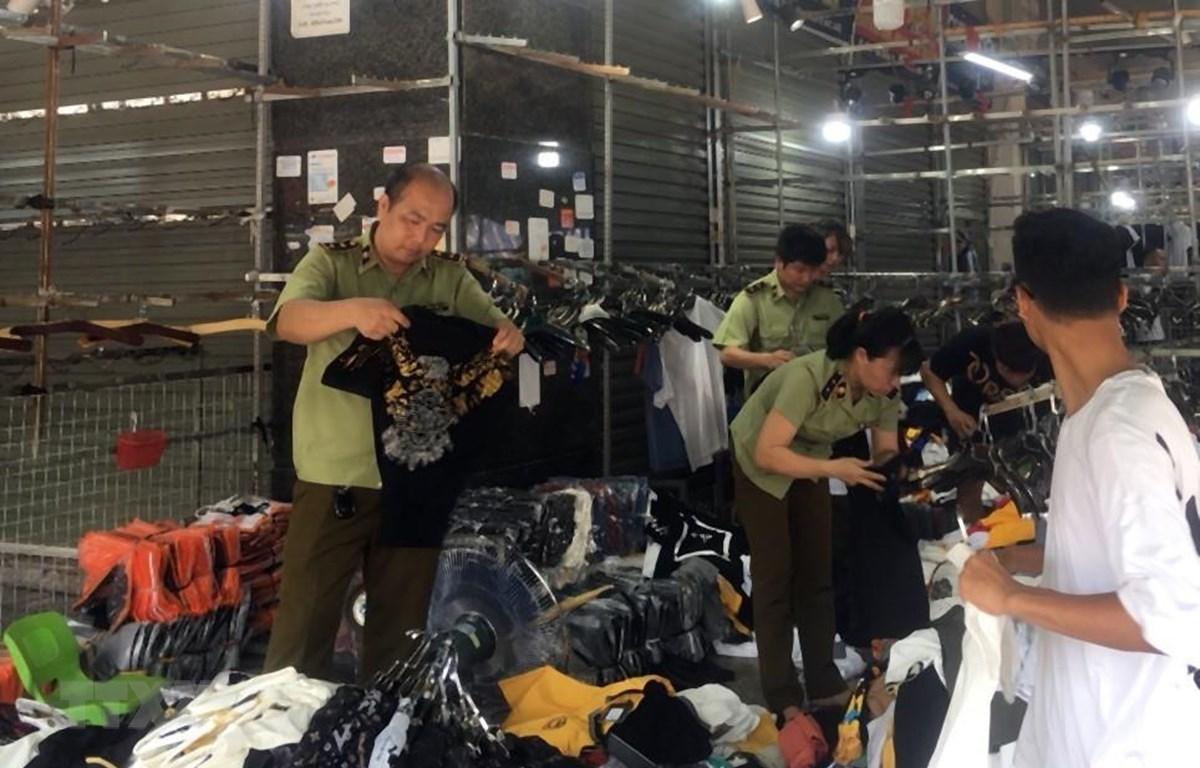 Lực lượng chức năng kiểm tra một cửa hàng kinh doanh quần áo tại chợ Ninh Hiệp. (Ảnh: TTXVN phát)