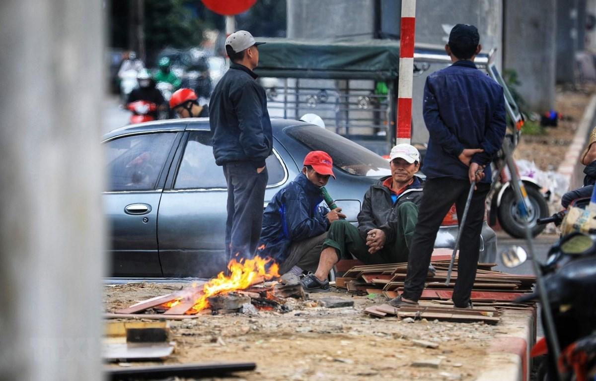 Người lao động đốt củi sưởi ấm khi nhiệt độ xuống thấp. (Ảnh: Thành Đạt/TTXVN)