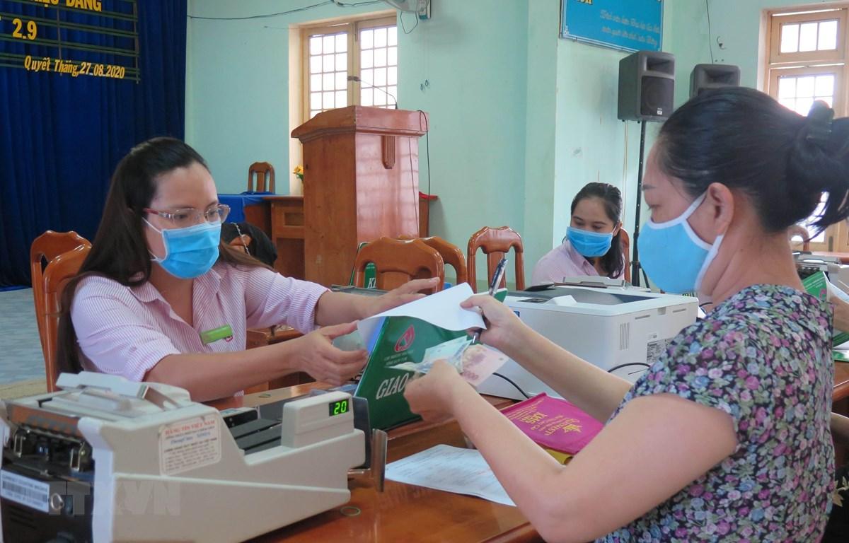 Người dân phường Quyết Thắng, thành phố Kon Tum làm thủ tục nhận tiền vay vốn tín dụng chính sách. (Ảnh: Dư Toán/TTXVN)
