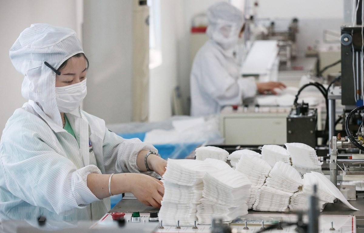 Công nhân sản xuất khẩu trang tại một nhà máy ở tỉnh Giang Tô, miền đông Trung Quốc, ngày 14/5/2020. (Ảnh: AFP/TTXVN)