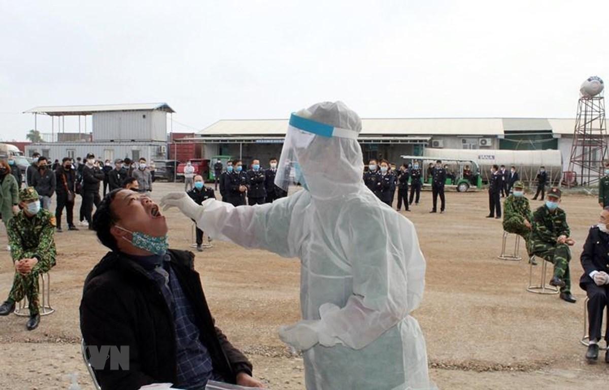 Bác sỹ lấy mẫu xét nghiệm SARS-CoV-2 cho cán bộ, người lao động làm việc, lao động tại Bắc Luân II, thành phố Móng Cái. (Ảnh: TTXVN)