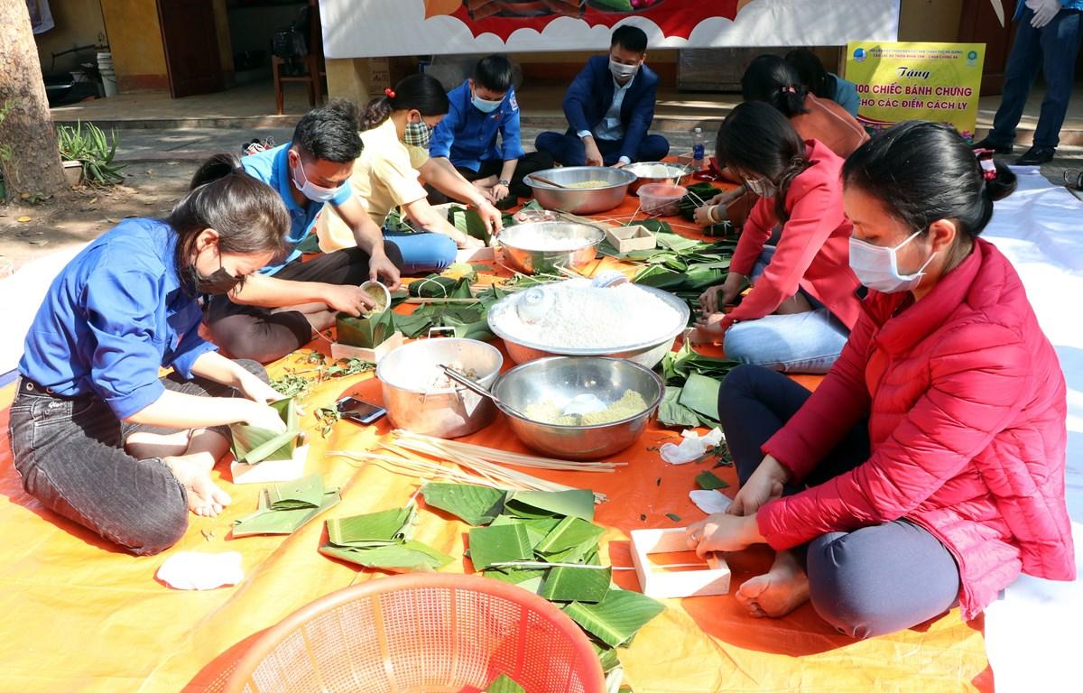 Các tình nguyện viên gói bánh chưng gửi cho những người trong khu cách ly ở Hải Dương. (Ảnh: Mạnh Tú/TTXVN)