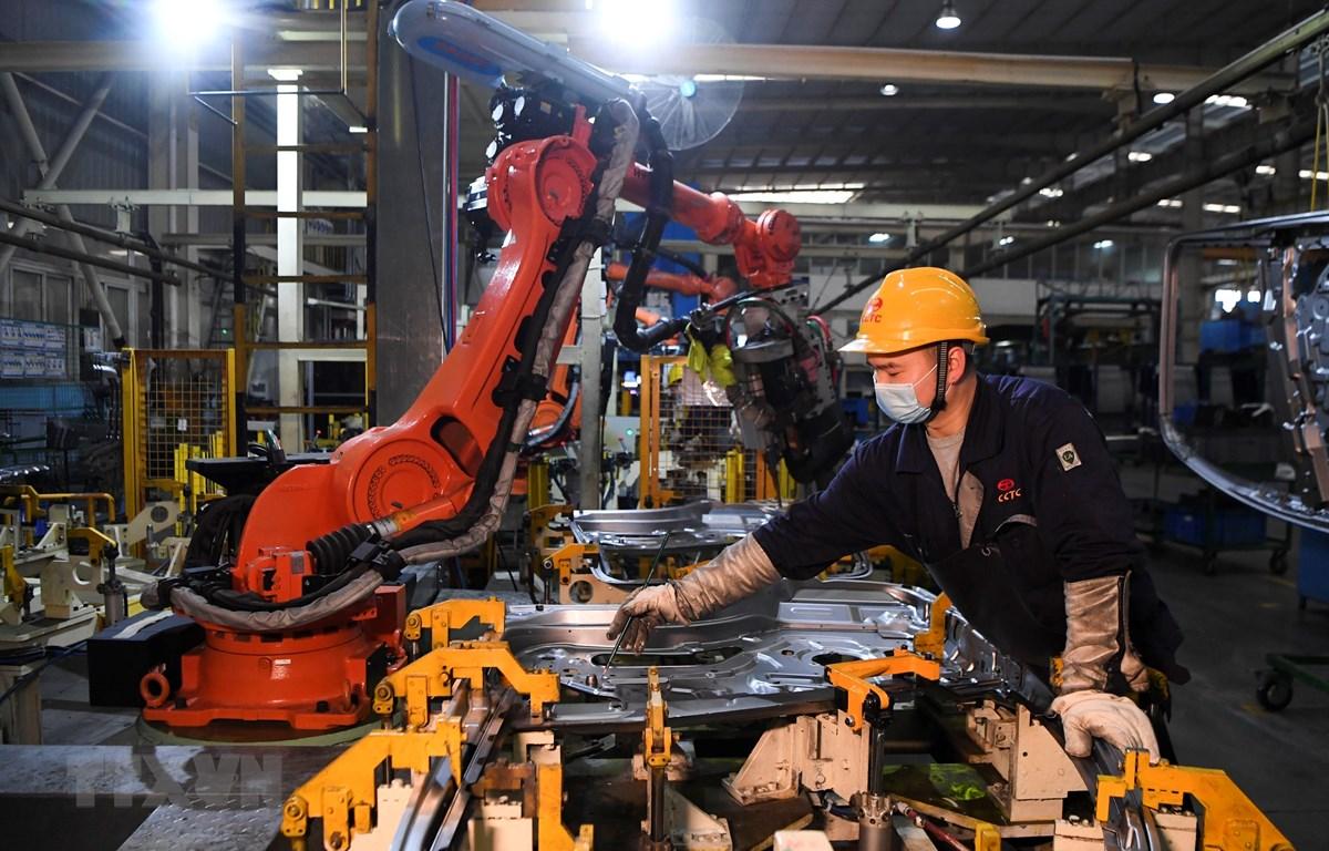 Công nhân làm việc bên trong một nhà máy ở Du Bắc, tỉnh Trùng Khánh, Trung Quốc ngày 11/3/2020. (Ảnh: THX/TTXVN)